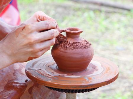 loamy: Potter makes on pottery wheel clay pot.Taken closeup. Stock Photo