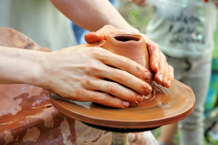loamy: Potter hands taken closeup on pottery wheel clay pot.Pottery manufacturing process.