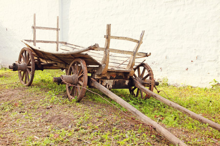 yesteryear: Vintage old rough wooden cart in front of old clay wall.Toned image.