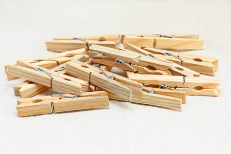 clothespins: Wooden clothespins heap taken closeup on white fabric background.