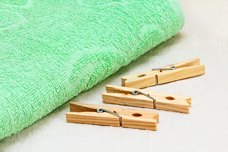 terrycloth: Green towel and wooden clothespins on white fabric background.