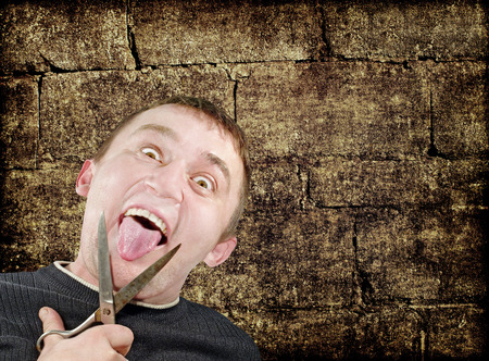 off cuts: Mad man with scissors cuts off itself tongue on grunge brick wall background.