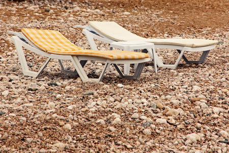 chaise lounge: Dangerous vacation.Two vacant chaise lounge on the beach. Stock Photo