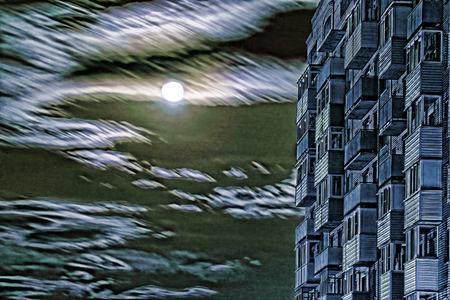 moonrise: Multistory house against of dramatic full moon sky.Digitally altered image.