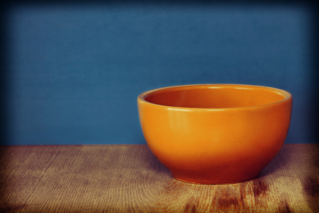 tureen: Ceramic plate, soup tureen on wooden surface against of blue background.Toned image. Stock Photo