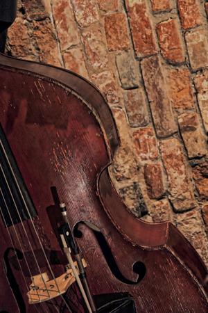 toned image: Contrabass near old brick wall.Retro style toned image. Stock Photo