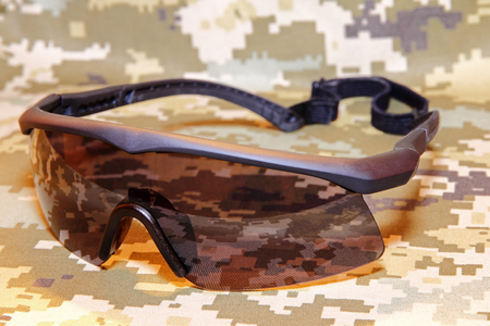 defense facilities: Military tactical goggles on camouflage background.