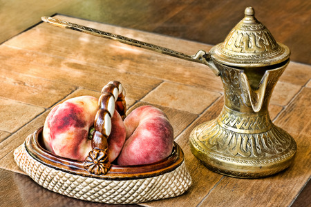 toned image: Retro arabian style brass coffee pot and ceramic vase with peaches on a table.Soft toned image.