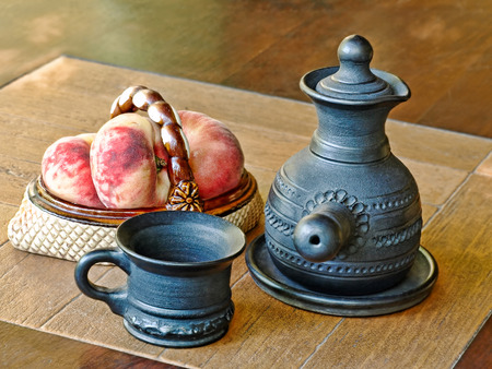 loamy: Arabian style coffee pot and peaches in ceramic vase on a table.