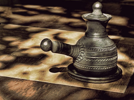 loamy: Black ceramic arabian style coffee pot on wooden table and spots of sunlight.
