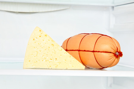 appetizing: Appetizing cheese and sausage on refrigerator shelf taken closeup.