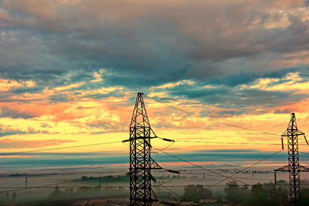 torres eléctricas: Two electricity pylons against of dramatic sunset sky taken closeup.