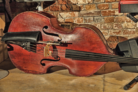 fingerboard: Contrabass on concert stage near old brick wall.Retro style toned image. Stock Photo