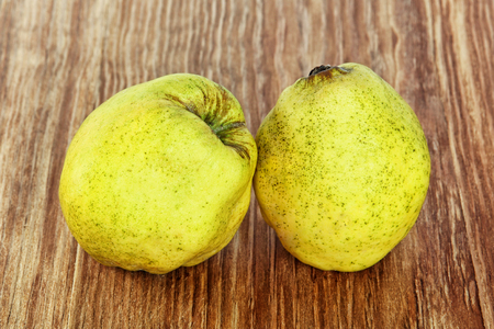 pectin: Two appetizing ripe quince on grunge wooden background taken closeup. Stock Photo
