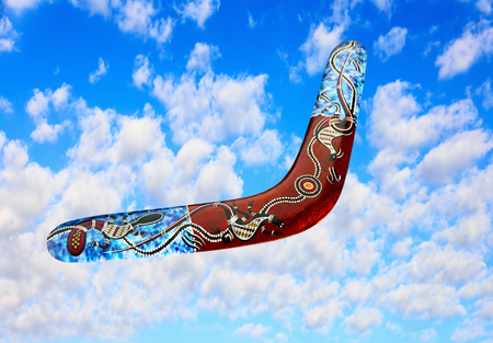 aerodynamic: Multicolored australian boomerang flies in sky against of pure white clouds.