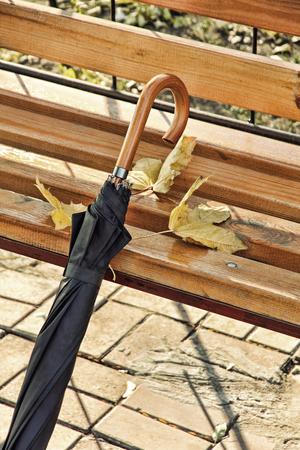 Black umbrella near wooden park bench taken closeup.Toned image. Stock Photo