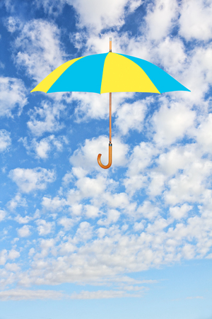 brigth: Wind of change concept.Umbrella in Ukrainian flag colors flies in sky against of white clouds.Mary Poppins Umbrella.