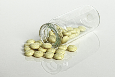 Prescription Medication Pain Pills spilled out of Glass Drug Bottle on white background.Digitally altered and toned image. Stock Photo