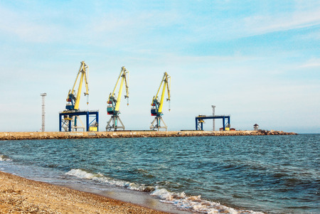 Three dock cranes in seaport against of the blue sky and coastline. Stock Photo