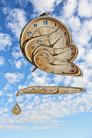 thawing: Liquid and flexible time concept.Surreal Alarm clock transforming and thawing on blue cloudy sky background.