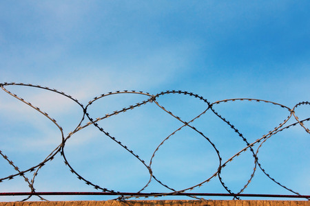 Barbed wire wall against of the blue sky taken closeup. Stock Photo