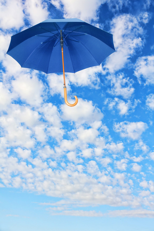 Mary Poppins Umbrella.Blue umbrella flies in sky against of white clouds.Wind of change concept. Stock Photo