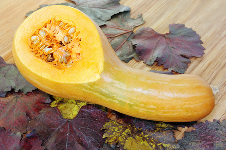Yellow sliced Pumpkin on color autumn foliage and wooden background.