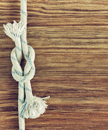 White rope and nautical reef knot on grunge wooden background.Empty space for text.