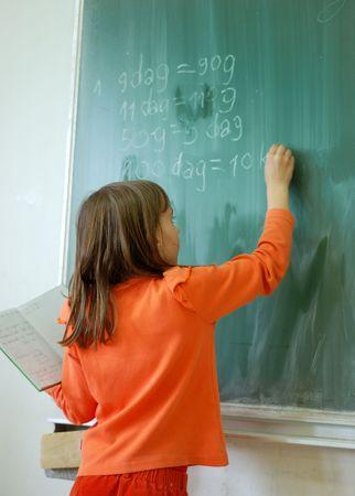 Girl writting on the school table Stock Photo - 5065385