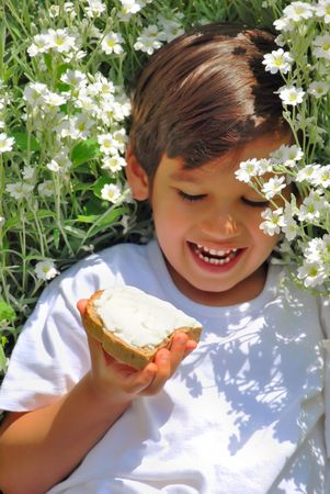 A little kid holding bread with white cream on Stock Photo - 5100539