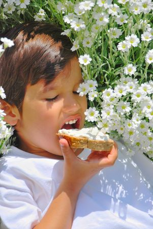 A little kid holding bread with white cream on Stock Photo - 5100541