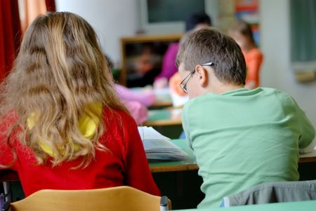 Mail and female two children learning at the school desk Stock Photo - 5100542