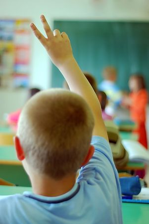 Child rising two fingers for answer at school photo