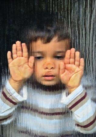 children sad: A little sad kid looking through glass Stock Photo