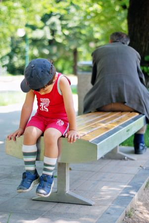 Little kid in opposite with an old man on bench photo