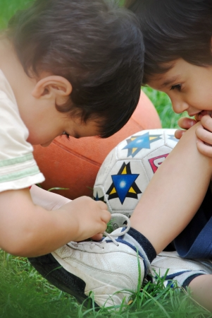 trying on: Kid helping his brother about tying his shoe laces Stock Photo