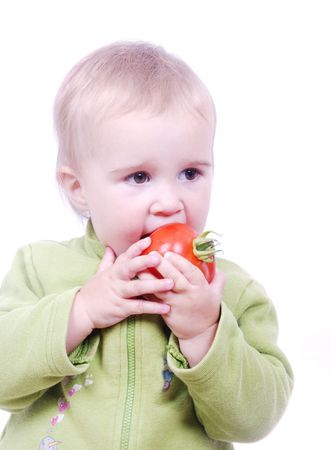 A little cute girl is eating a red tomato Stock Photo - 5142163