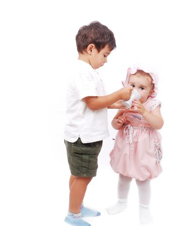 A little kid is feeding his sister Stock Photo - 5142396