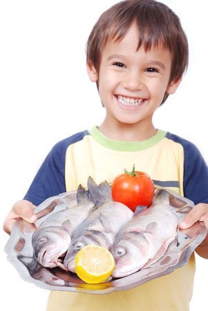 Smiling kid with three fresh fishes on table photo