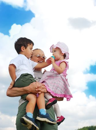 armful: grandmother holding two kids in her armful Stock Photo
