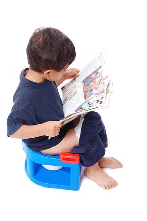 A little cute boy is sitting on toilet and reading newspaper with pictures photo