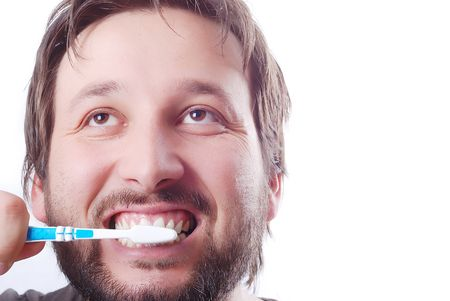 Young man is cleaning his teeth with brush photo