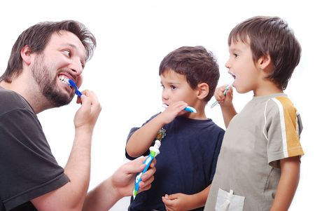 Father is teaching his son hot to clean the teeth properly photo