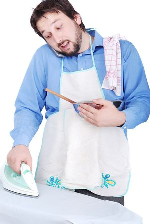 Good man is ironing, cooking and speaking on phone Stock Photo - 5142470