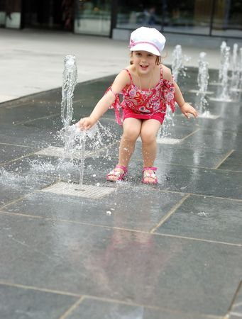 Happy beautiful girl playing with fountain in front of building photo