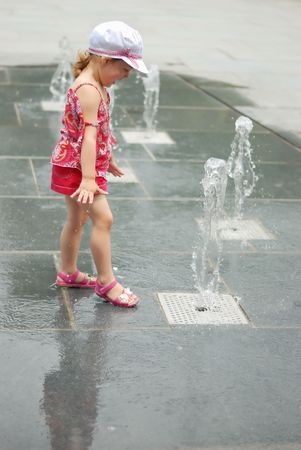 kids playing water: Happy beautiful girl playing with fountain in front of building