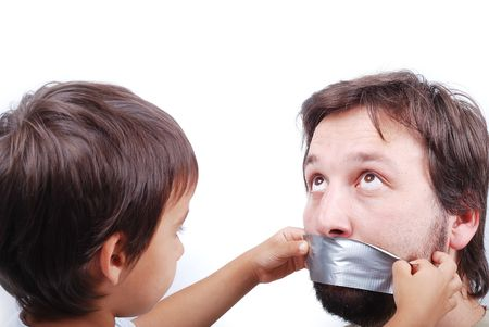 shutup: Clever son is putting a strip on fathers mouth Stock Photo