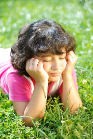 A little female child laying on the grass outdoor Stock Photo - 5781916