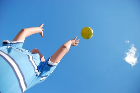 throw up: A young male child playing with the ball