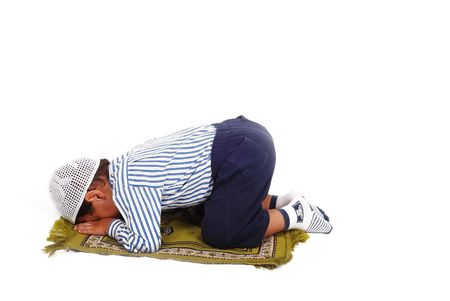 A little muslim kid is praying on traditional way photo